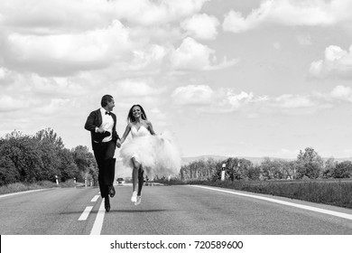 young wedding happy couple of sexy girl with brunette hair and pretty face in white bride dress and handsome man in black groom suit running on road way on cloudy blue sky background, copy space