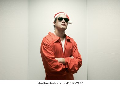 A young weird cool guy with a prisoner's jumpsuit, sunglasses and santa hat on.