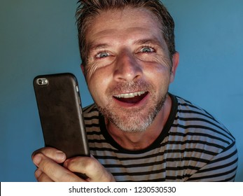 young weird and crazy mobile phone addict man using cell compulsively with weird and freak face expression in internet social media addiction and obsession isolated on even background