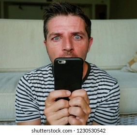 young weird and crazy mobile phone addict man using cell compulsively with weird and freak face expression in internet social media addiction and obsession