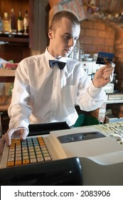 young weiter, barman verifying credit card or cheating alcohol