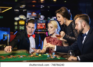 Young, well dressed and rich people playing roulette in the casino