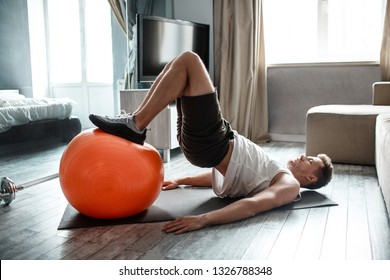 Young well-built man go in for sports in apartment. Guy hold legs on fitness ball and doing lifting up with body. Strong hardworking man.