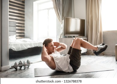 Young well-built man go in for sports in apartment. He lying on carimate and does abs workout. Guy hold hands behind head. Intensive workout.
