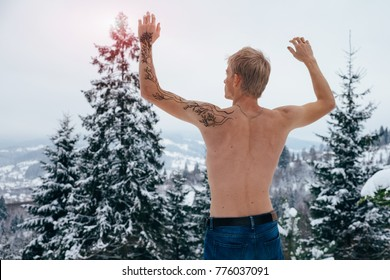 Young well-built man shot from back standing shirtless with raised arms,one of which is covered with mehndi ornament in wild nature of Carpathian mountains on a winter day.