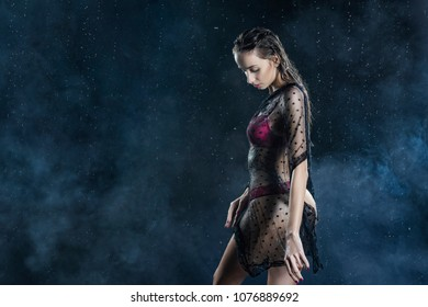 Young wet slim girl wearing a red lingerie and black translucent veil posing sideways in rain water drops in a studio shows her beautiful butt on black in a theatrical smoke. Healthy skin. Copy space