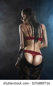 Young wet slim girl wearing a red lingerie and black veil poses from her back in rain water drops in a studio shows her beautiful butt on black in a theatrical smoke. Healthy smooth skin. Copy space