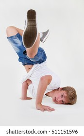 Young white b-boy dancing break dance.Little hip hop dancer guy isolated on white.Good looking teenager breaker posing in the studio on cut out white background.Cool teenage male model break dancing