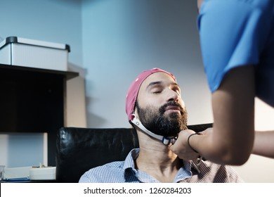 A young white bipolar man with visits a clinic for an electroencephalogram. Medical staff performs an EEG on Caucasian bearded male. Moment when cap is put on. Mental health and disease