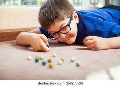 Young white boy playing with marbles and aiming at one at home