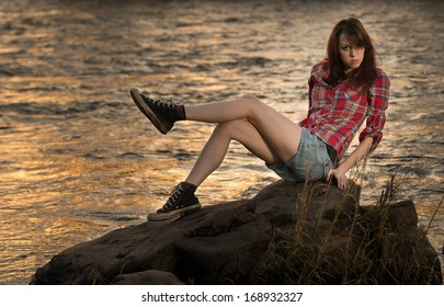 A young white caucasain female sitting on a rock near a river during sunset with her legs up.