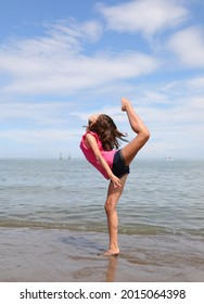young white caucasian girl doing rhythmic gymnastics exercises on the beach in summer
