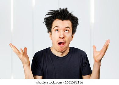 Young white caucasian guy long hair shrug his shoulders and looking up on a white background.