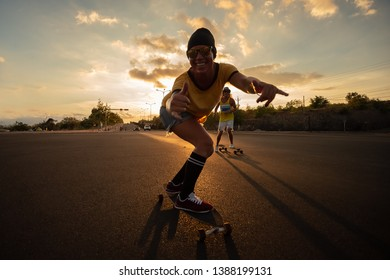 A young white Caucasian skateboarders ride skateboards at sunset