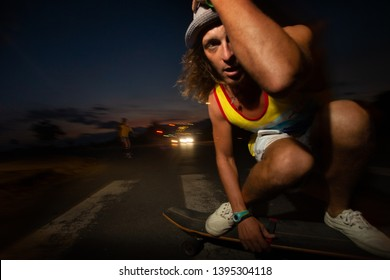A young white Caucasian skateboarders ride skateboards at night