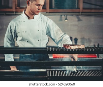 Young white chef in apron standing near the brazier whith coals. Man cooking beef steak in the interior of modern professional kitchen