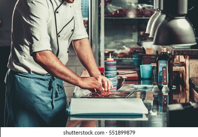 Young white chef in kitchen interior. Man marinating beef steak on a tray. Meat ready for the grill and serve. Only hands