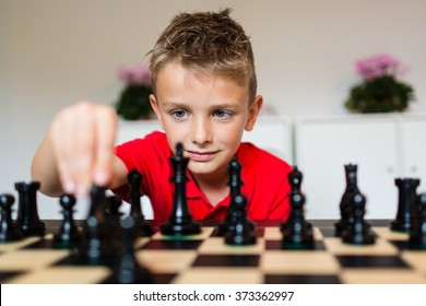 Young white child playing a game of chess on large chess board.