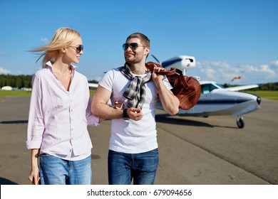 Young white couple smiling while walking on runway from personal air plane. Attractive models wearing trendy clothes, smart watch and brown leather bag. Motor tourist seaplane