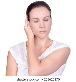 Young white deaf or hearing impaired woman with eyes closed holding her hand over her ear to shut out noise on white background in studio