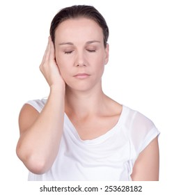 Young white deaf or hearing impaired woman with closed eyes holding her hand over her ear to shut out noise on white background in studio