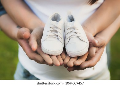 Young white family waiting birth of their first baby. Pregnant woman and man dreaming about son or daughter. People holding small white cotton shoes in hands. Happy parents concept.