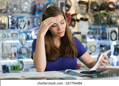 Young white female entrepreneur running a small business and working in computer shop, checking bills and invoices with worried expression