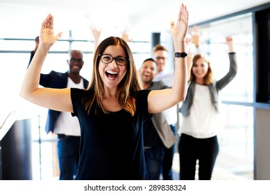 Young white female executive standing in front of colleagues with their arms raised up.