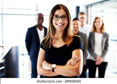 Young white female executive standing in front of colleagues with arms crossed and smiling