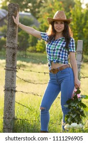 Young white girl in country style dress with flowers leaning on fence