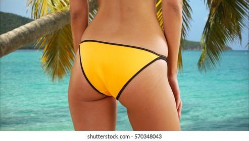 Young white girl poses on the Caribbean beach in her yellow bikini