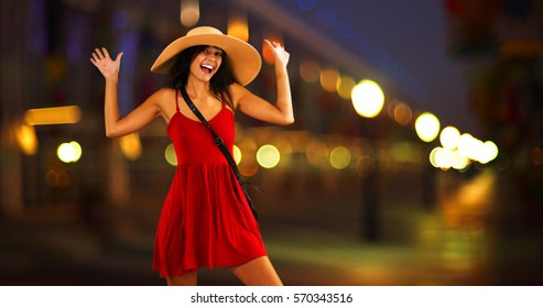 Young white girl standing on the pier in a red sun dress and floppy hat