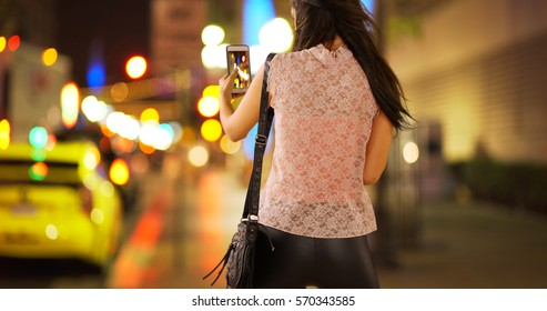 Young white girl taking a photo of the lights at night