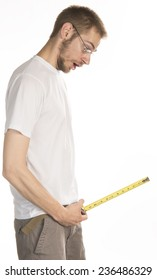 Young white male in his 20s holds a measuring tape near his groain