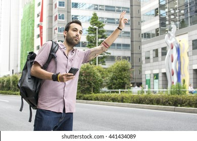 Young White Man Holding Cellphone Hailing Uber Taxi