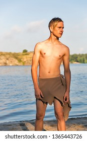 young white man in loincloth on the background of sand river beach