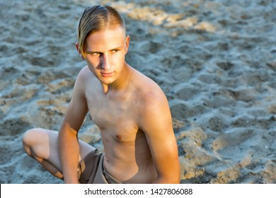 young white man in loincloth on the background of sand beach