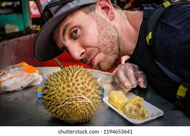 A young white man looks at the camera with a curious look while eating spikey, stinky durian fruit with a plastic glove in Kuala Lumpur, Malaysia