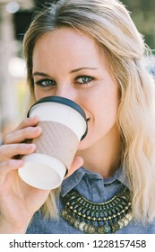 Young white millennial female sips a cup of coffee
