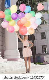 Young white woman with colorful latex balloons, urban scene, outdoors