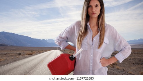 Young white woman in need of petrol looking at camera outside on desert highway