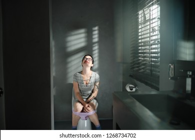 A young white woman smiles with relief and satisfaction after being able to empty her bladder in the toilett. Attractive short haired woman with tattoos sitting on toilett smiling with underwear down