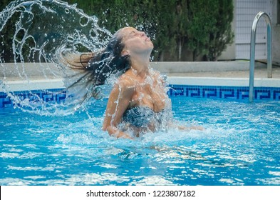 Young white woman splashing water with her hair in the pool