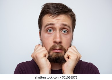 Young wide-eyed bearded man pulling at his long messy beard in frustration and stress