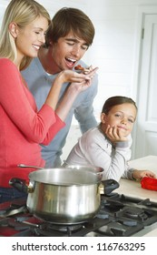 A young wife allows her husband to taste the sauce she is cooking for their dinner while their young daughter smiles at their antics