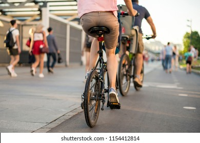 young wife and husband riding bikes in the europe street during summer season
