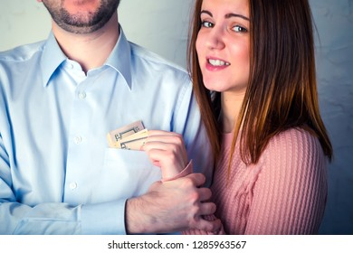 young wife pulls out dollar bills from her husband's shirt pocket, husband grabbed her hand and does not allow to pull out the money.