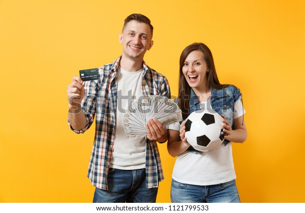 Young win couple, woman man, football fans holding bundle of dollars money, credit card, soccer ball, cheer up support team isolated on yellow background. Sport bet, ardor family lifestyle concept