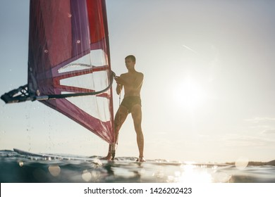 Young windsurfer catch the wind on windsurf board. Windsurfing, sailing, surfing, extreme sports