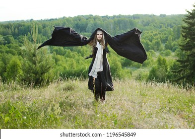young witch in a black robe stands on a grassy hill, raising her hands to the sky